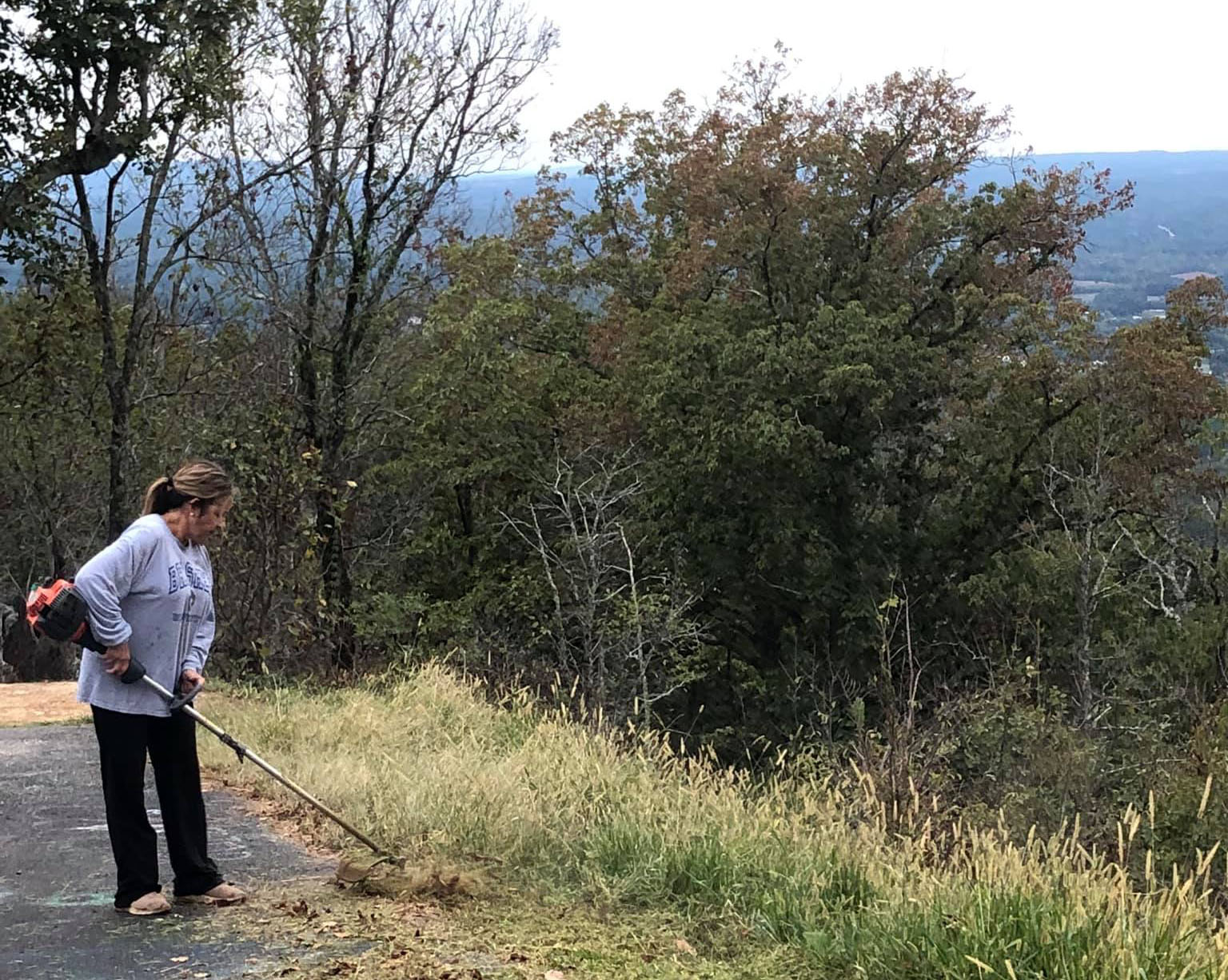 Christine Brasher, pictured above, weed eating the grass along the Chimney Peak Mountain. (Courtesy of Christine Brasher)