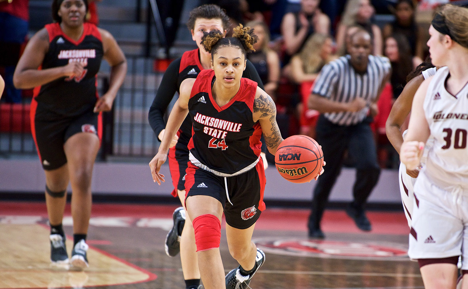 Female basketball player in Jacksonville State University uniforms dribbles basketball down court at a basketball game. Several other players can be seen in the background, none in focus.