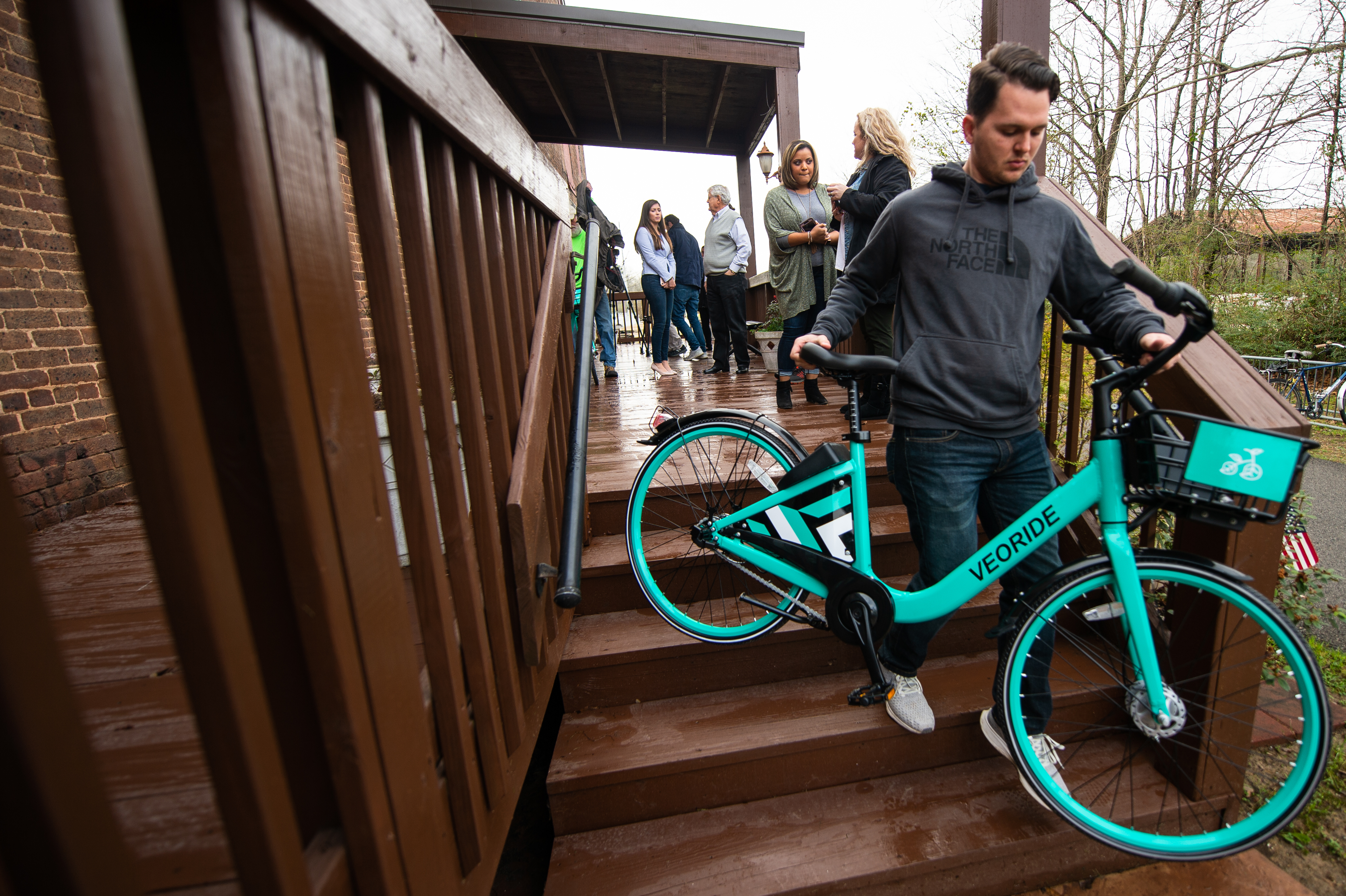 VeoRide Fleet Coordinator Trent Dickeson, pictured right, carries a VeoRide bicycle at the Jacksonville Train Depot during a ribbon cutting ceremony for the bike share program. (Matt Reynolds/JSU)