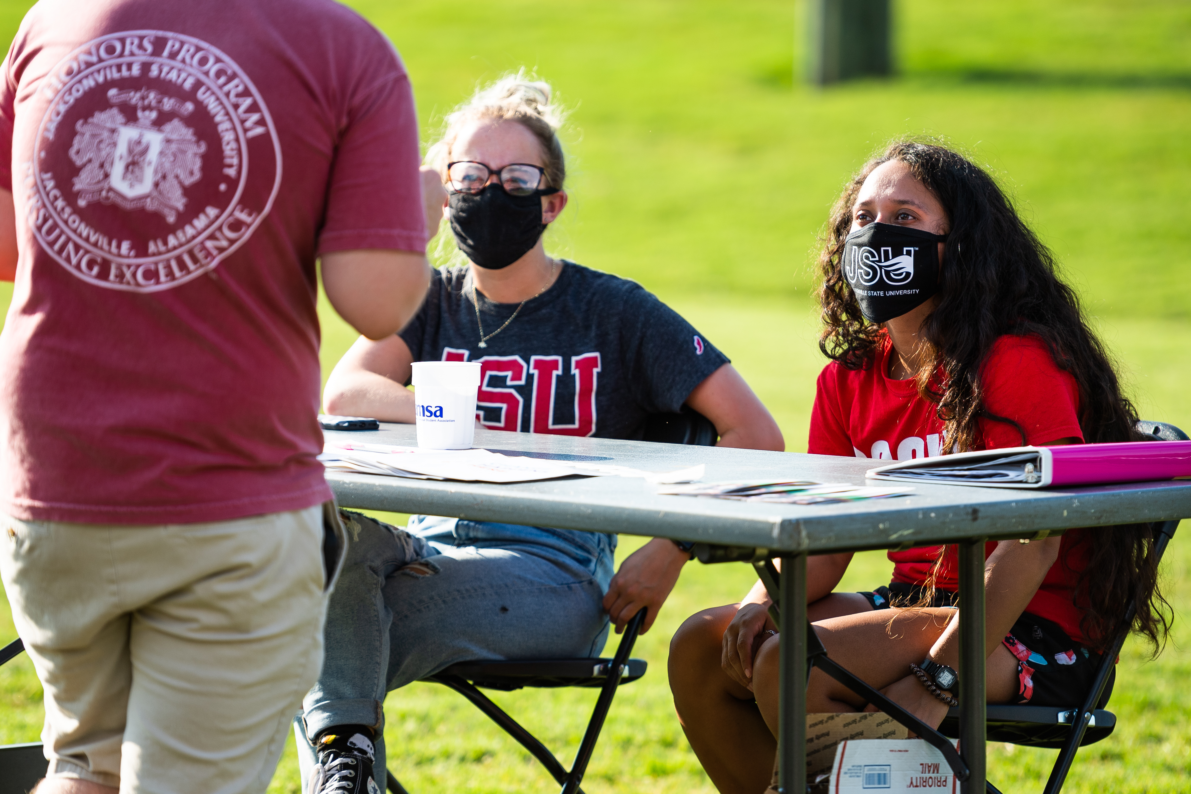 Students converse with one another at a table during JSU's Get on Board Day on Aug. 18. The university announced Wednesday that all in-person student organization events would be suspended for two weeks. (Matt Reynolds/JSU)