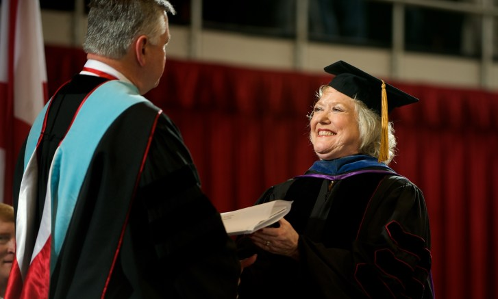 Claudia McDade walks across the stage to receive her Emeriti Faculty award from JSU President William Meehan on Dec. 19, 2008. (Steve Latham/JSU)