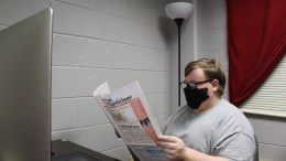 Editor in Chief Scott Young, pictured, reads a newspaper in The Chanticleer's office in Self Hall. Young is graduating with a bachelor's degree in communication on May 7. (Courtesy of Rebekah Ledbetter)