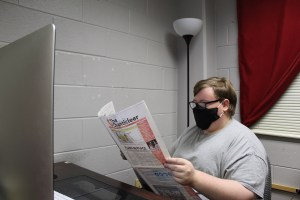Editor in Chief Scott Young, pictured, reads a newspaper in The Chanticleer's officer in Self Hall. Young is graduating with a bachelor's degree in communication on May 7. (Courtesy of Rebekah Ledbetter)